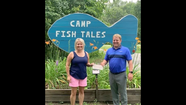 Shannon Forshee, Executive Director at Camp Fish Tales, accepts a check from Karl Ieuter, of the Ieuter Insurance Group and Hastings Mutual Insurance Company, for $4000.                                                                                --Courtesy Photo