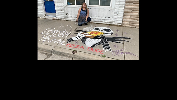 """REBECCA LOWE, Pinconning's resident Chalk Artist was at it again on Saturday, this time with a Halloween themed scene in front of Pizza Dude on Kaiser Street.          Her pizza-loving skeleton/vampire directs passersby into the shop for some """"Spooky Good Pizza"""". This is the latest of four different scenes created by Lowe around Pinconning this year. --Courtesy Photo"""