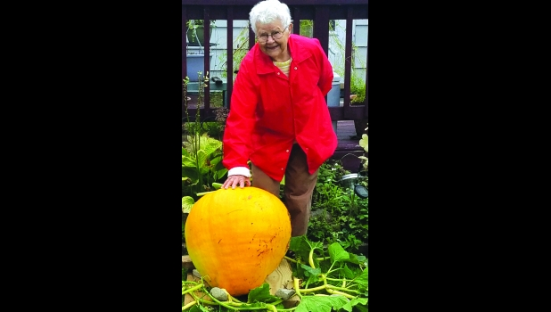 CAROLINE SKARBEK poses with the 40+ pound pumpkin she grew.